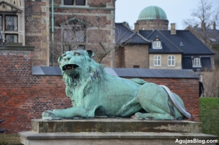 Lion statue at the entrance to Rosenborg Castle. A moat surrounds the castle past this entrance.
